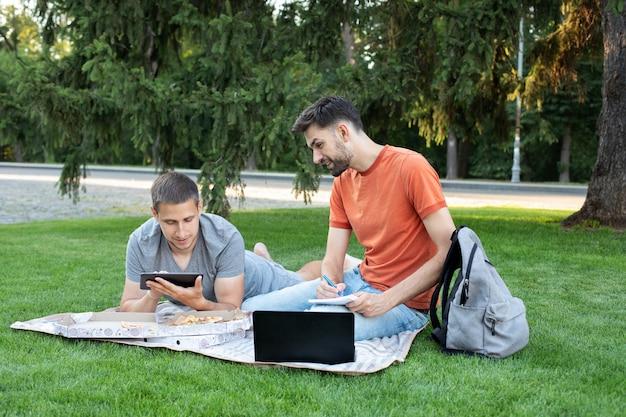 Homem explicando algo para a amiga no laptop. alunos estudando no parque e sorrindo.
