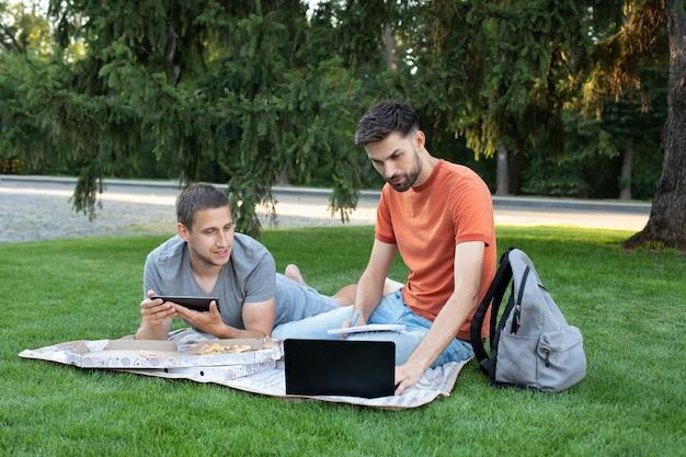 Homem explicando algo para a amiga no laptop. alunos felizes estudando no parque e sorrindo.