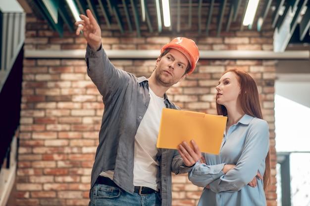 Homem explicando mostrando plano de construção para a mulher