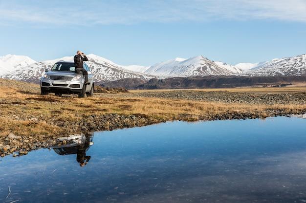 Homem explorador na islândia sentado no carro