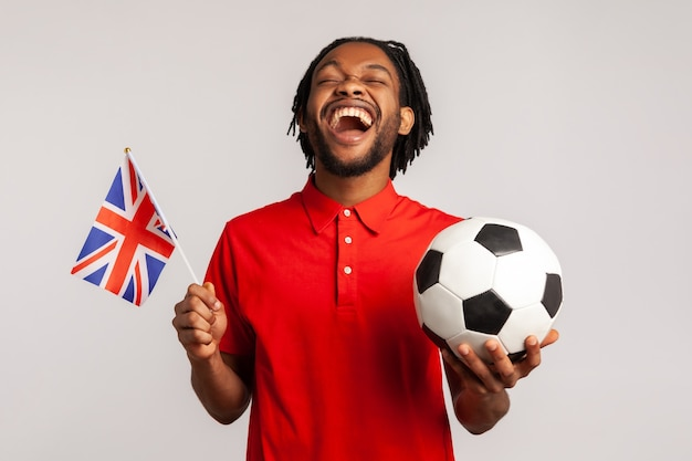 Homem extremamente feliz com a bandeira britânica torcendo por seu time favorito, regozijando-se pela vitória.
