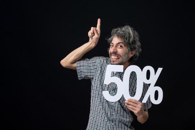 Homem exultante de frente apontando o dedo para cima e segurando uma marca na parede escura