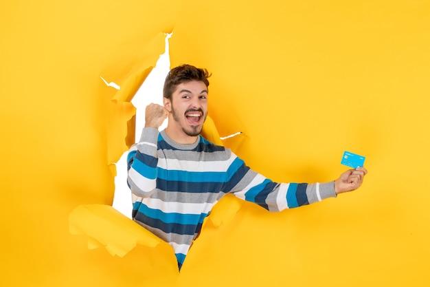 Homem exultante de frente segurando um cartão na mão através da parede amarela de papel rasgado
