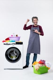 Homem exultante de vista frontal segurando um cartão em pé perto de uma máquina de lavar no fundo branco