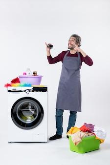 Homem exultante de vista frontal segurando um cartão em pé perto do cesto de roupa suja da máquina de lavar no fundo branco