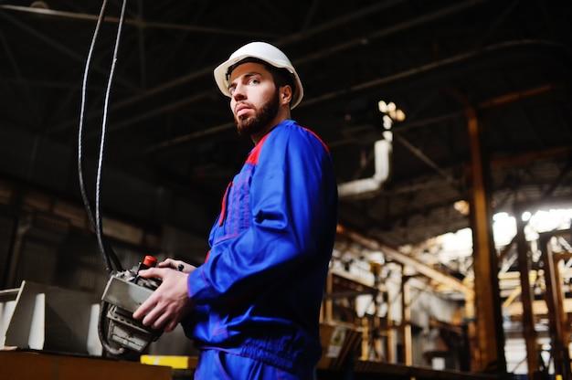 Homem, fábrica, controle remoto nas mãos