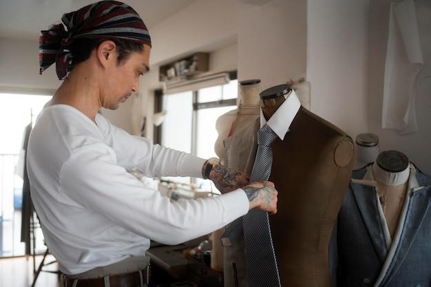 Homem fabricando roupas tiro médio