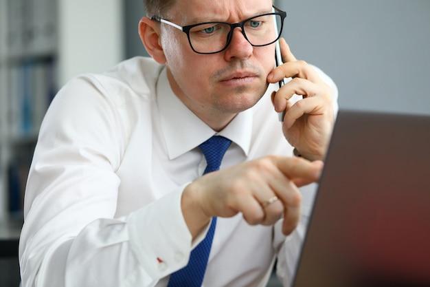 Homem fala ao telefone e aponta para a tela do computador.