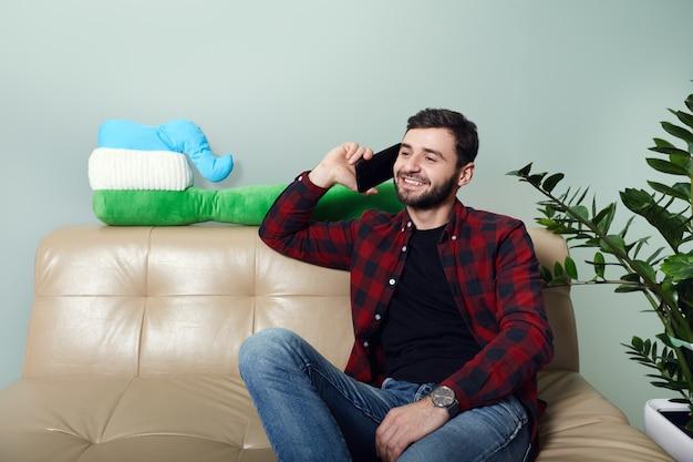 Homem fala no smartphone enquanto espera na recepção de uma clínica odontológica moderna
