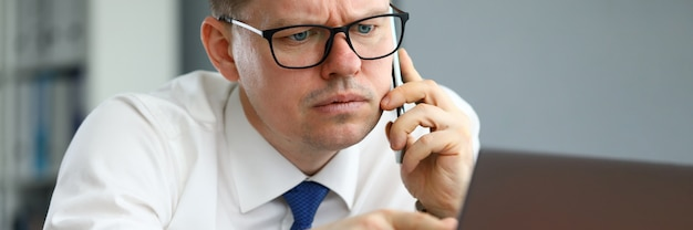 Homem fala no telefone e aponta para a tela do computador