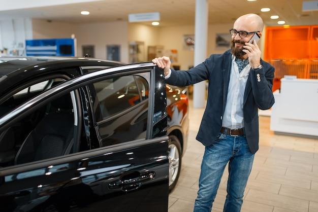 Homem fala por telefone celular perto de automóvel novo na concessionária. cliente no showroom de veículos, homem comprando transporte, concessionária de automóveis