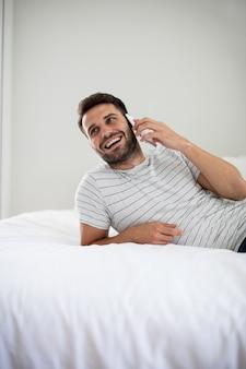 Homem falando ao celular no quarto de casa