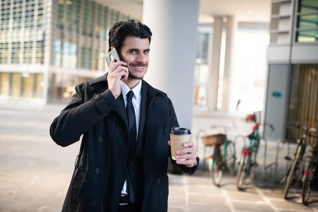 Homem falando ao telefone e segurando uma xícara de café enquanto caminhava em uma cidade