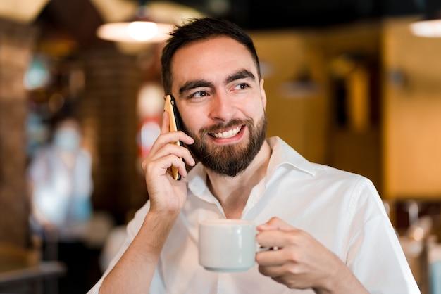 Homem falando ao telefone enquanto bebe uma xícara de café em uma cafeteria.