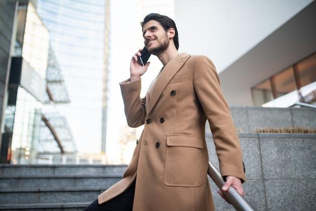 Homem falando ao telefone enquanto descia uma escada
