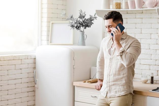 Homem falando ao telefone na cozinha