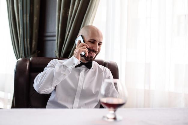 Homem falando ao telefone no restaurante.