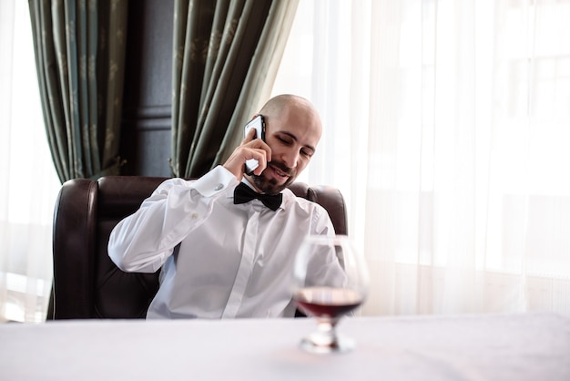 Homem falando ao telefone no restaurante