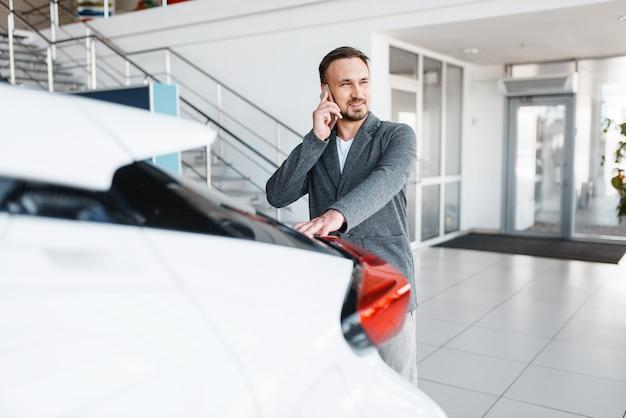 Homem falando ao telefone perto do carro novo no showroom