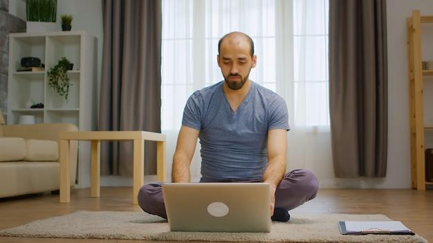 Homem falando com seus amigos no laptop de videochamada no chão sobre o coronavírus.