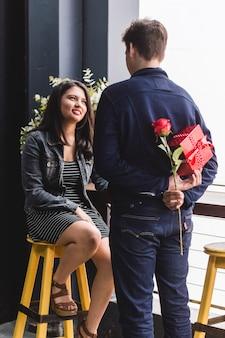 Homem falando com sua namorada e se escondendo em suas costas um presente e uma rosa