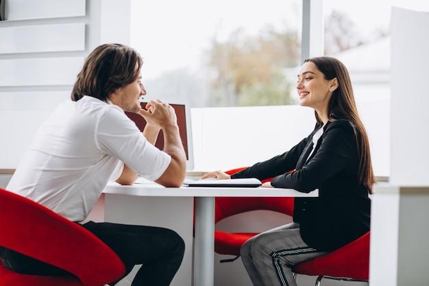 Homem falando com vendedor feminino em uma sala de show de carro