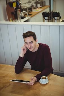 Homem falando no celular e segurando um tablet digital