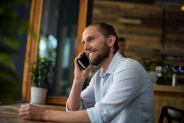 Homem falando no celular em café