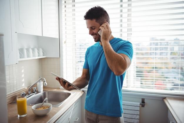 Homem falando no celular enquanto usa o tablet digital na cozinha