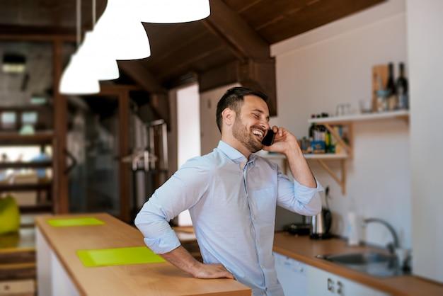 Homem falando no celular na cozinha