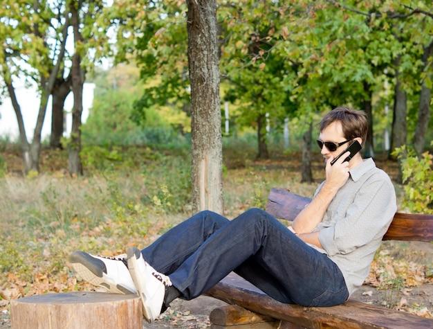 Homem falando no celular, sentado, relaxando em um banco de madeira no campo, com os pés no toco de uma árvore