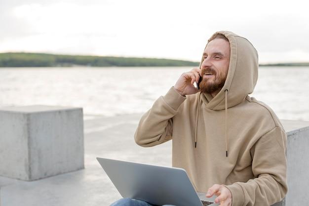 Homem falando no smartphone ao lado do lago com laptop