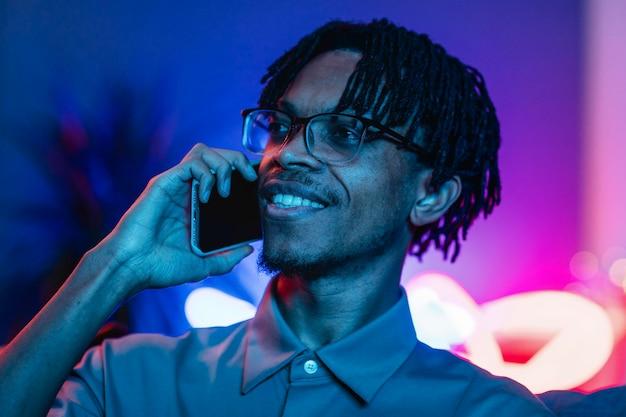 Homem falando no smartphone em casa Foto gratuita