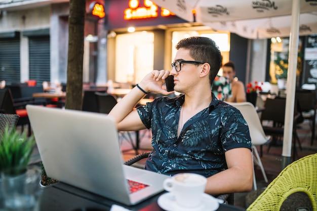 Homem falando no smartphone no café