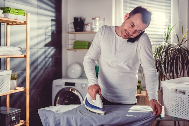 Homem falando no telefone enquanto passa a roupa