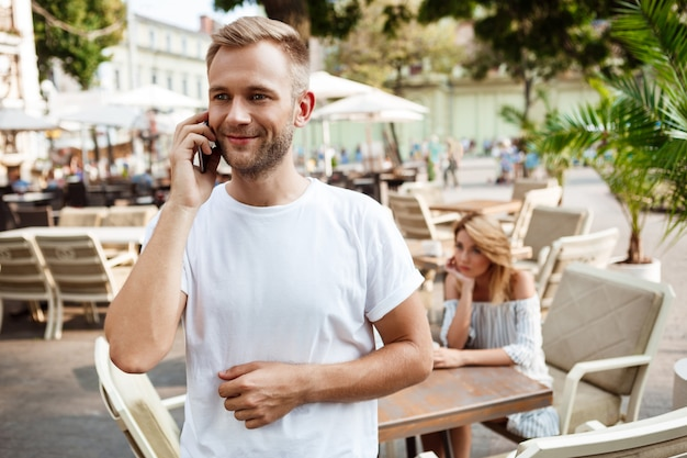 Homem falando no telefone enquanto sua namorada está entediada.