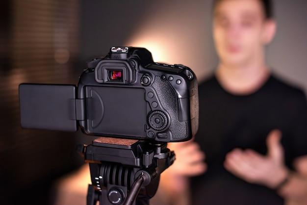 Homem falando para a câmera, gravando a si mesmo em um vlog. trabalhando em casa. jovem criador de conteúdo