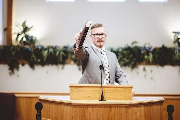 Homem falando perto de um suporte de discurso de madeira e segurando um livro nas mãos