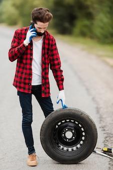 Homem, falando, telefone, segurando, pneu