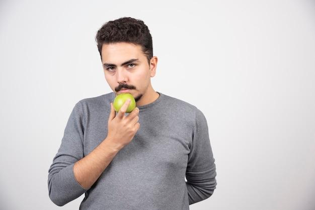 Homem faminto segurando maçã verde e olhando sério.