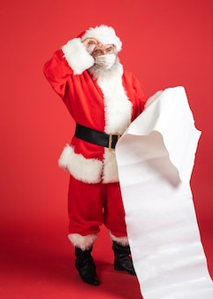 Homem fantasiado de papai noel com máscara médica segurando uma lista de presentes