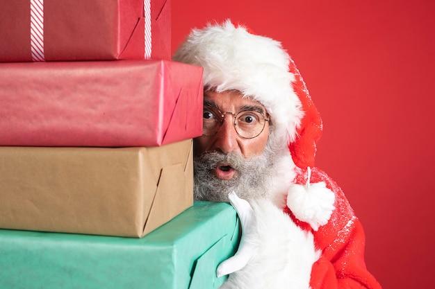Homem fantasiado de papai noel segurando presentes