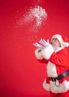 Homem fantasiado de papai noel soprando neve das mãos