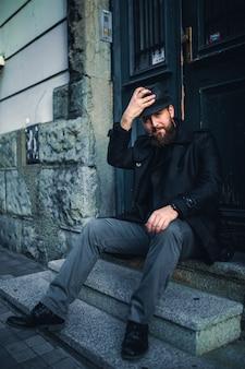Homem farpado considerável com o bigode que retorna em casa do trabalho, sentando-se nas escadas.