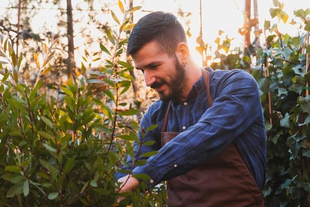 Homem farpado cuidando de plantas
