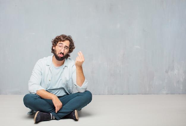 Homem farpado fresco novo que senta-se no assoalho. fundo da parede do grunge