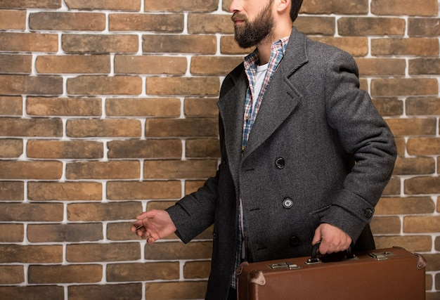 Homem farpado novo com uma mala de viagem contra a parede de tijolo.