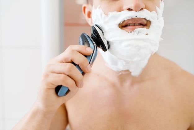 Homem faz a barba espumosa com barbeador elétrico no banheiro, rotina de higiene matinal.