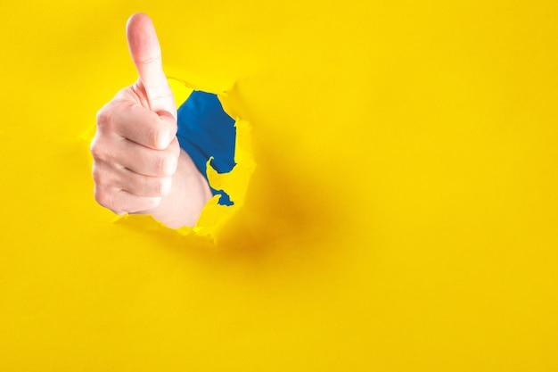 Homem faz o polegar para cima gesto, demonstra aprovação ou acordo, gestos através da parede de papel rasgado. sinal de mão. buraco na parede. como gesto