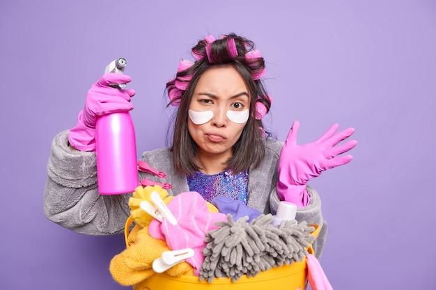 Homem faz penteado encaracolado com rolos aplica patches sob os olhos para reduzir rugas mantém a mão levantada usa luvas de proteção de borracha lava roupa em casa isolado na parede roxa